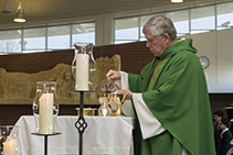 Father LaSalle readies the gifts at Mass.