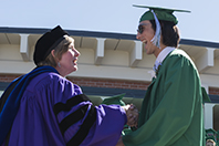 Dr. Alumbaugh congratulates a graduating senior.