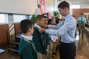 Upper classman bestows ties onto Academy 5th grader